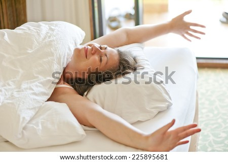 she woke up in the morning in bed and stretches - stock photo