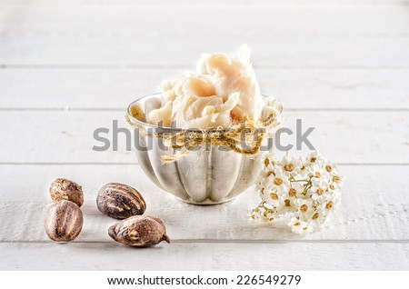 Shea butter and nuts on a wood - stock photo