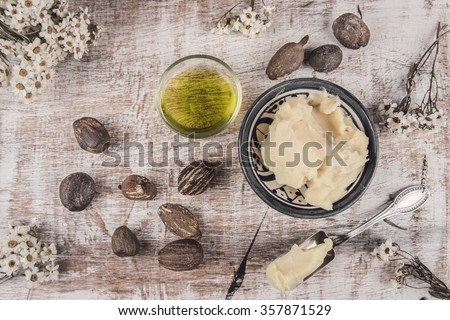 Shea butter and oil with shea nuts on a shabby white table with white flower and silver spoon - stock photo
