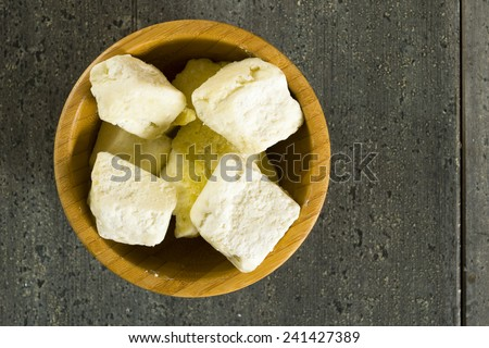 shea butter in bamboo bowl, dark wood table background - stock photo