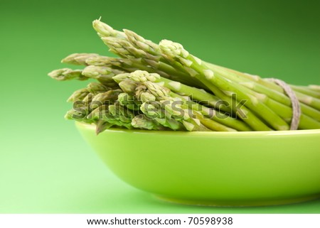 Sheaf of asparagus on a green background. - stock photo