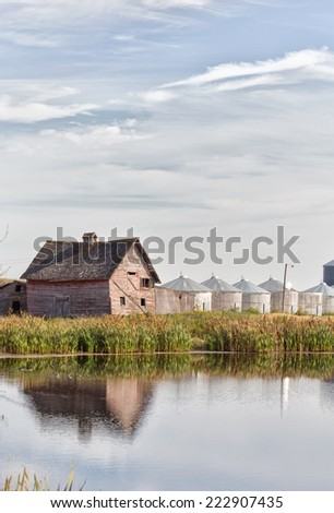 Shed and old grain bins reflected in pond - stock photo