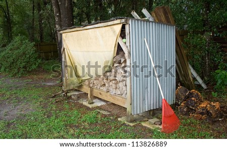 Shed with rake and wood for Fall season - stock photo