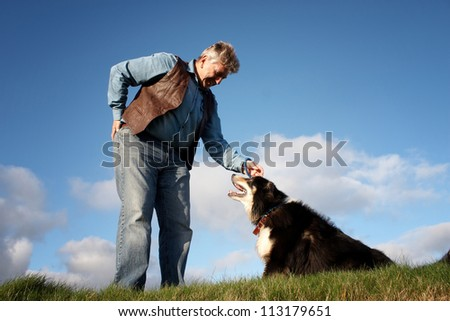 Sheep dog looking into the eyes of his owner - stock photo