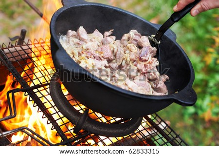 Sheep meat fried with onions in oil in a cauldron - stock photo