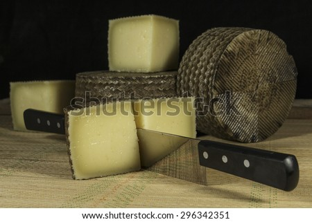 Sheep milk cheese cutted into pieces with double-handled knife - stock photo