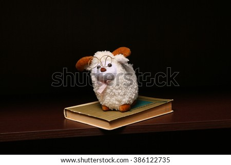 Sheep toy sits on stack of books. On the dark shelf.