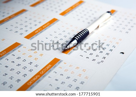 sheet of a calendar and a pen close-up