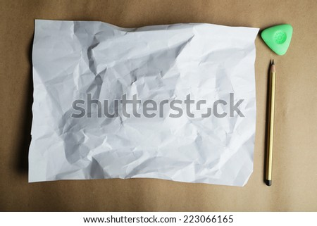 Sheet of blank paper and a pencil on brown background - stock photo