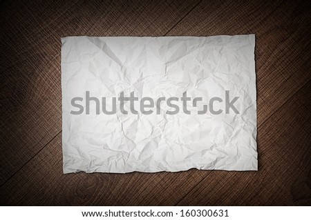sheet of crumpled paper on dark rusty brown wooden background - stock photo