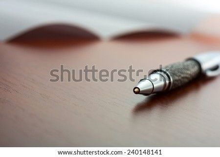 Sheet of paper and pen on the desktop - stock photo
