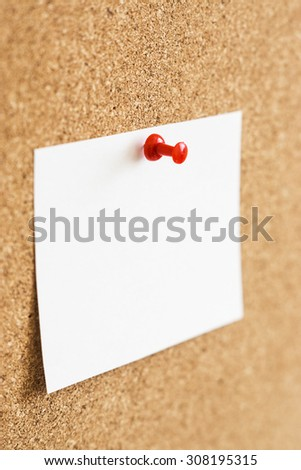 Sheet of paper on a cork pinboard with red plastic pin. Selective focus  - stock photo