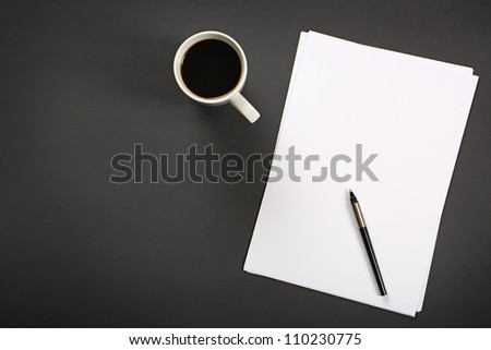 Sheet of paper, pen and cup of black coffee on black office desk. - stock photo