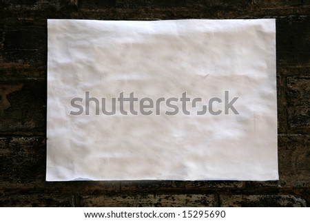 sheet of paper stuck on dark brick wall