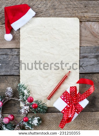 Sheet of paper with Christmas present and holly on wooden background - stock photo