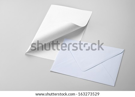 Sheet of paper with curled corner and envelope