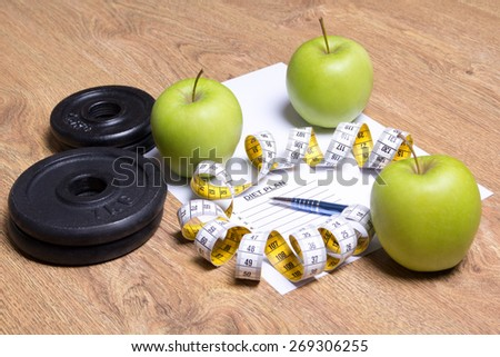 sheet of paper with diet plan, green apples, dumbbells and measure tape - stock photo