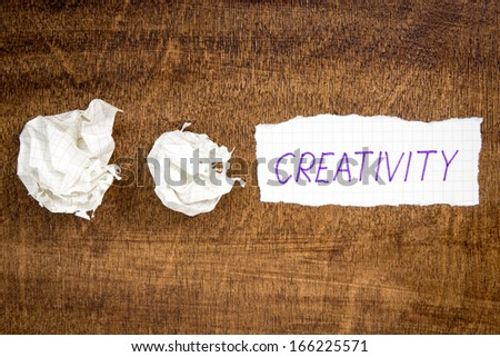 Sheet of paper with word CREATIVITY and crumpled wads on table - stock photo