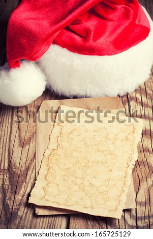 sheet of vintage paper with Santa's hat on wooden background - stock photo