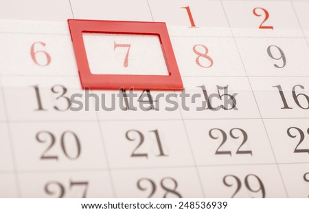 Sheet of wall calendar with red mark on framed date 7  - stock photo