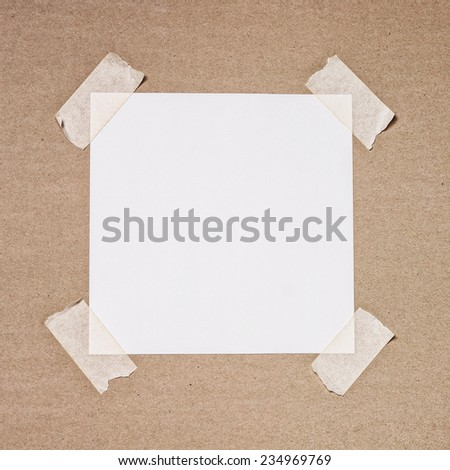 Sheet of white paper attached to the wall with scotch tape - stock photo