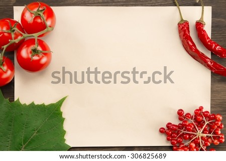 sheet old vintage paper with berries, tomatoes, chili pepper and grape leaves on wooden background . Healthy vegetarian food. Recipe, menu, mock up, cooking. - stock photo