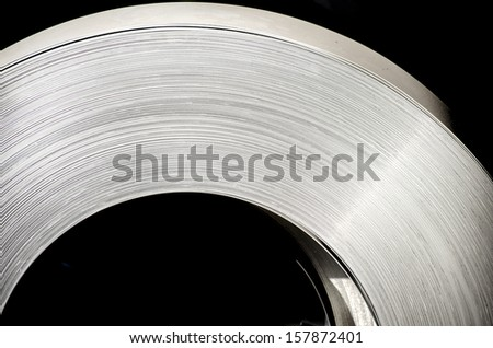 sheet tin metal roll on black background - stock photo