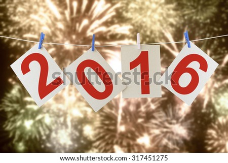 Sheets of a cardboard with numbers 2016 (New year of Two thousand sixteen ) hanging on a clothesline. With holiday fireworks in the blur background - stock photo