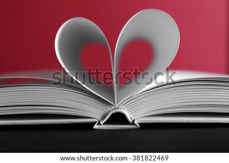 Sheets of book curved into heart shape on pink background - stock photo