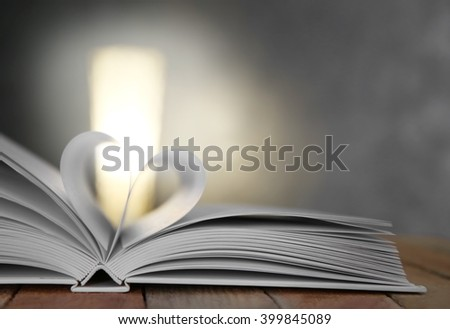 Sheets of book curved into heart shape on unfocused background - stock photo