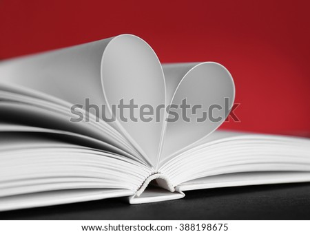 Sheets of book curved into heart shape on unfocused red background - stock photo