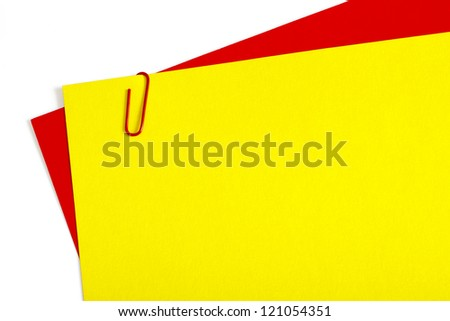 Sheets of color paper connected with red staple on white background - stock photo