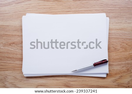 Sheets of white paper and a ballpoint pen on a light brown office desk close-up - stock photo