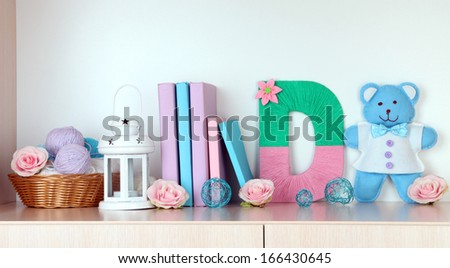 Shelf decorated with handmade knit letter - stock photo
