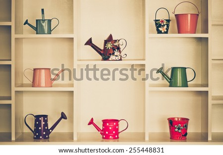 Shelf decoration with colorful gardening tools - watering cans, pail, bucket - stock photo