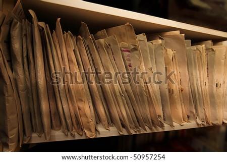 Shelf full of documentation filed in brown paper envelopes - stock photo
