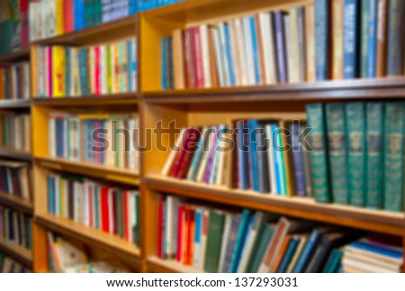 shelf with books in the library background. the image was blurred for use as a background. - stock photo