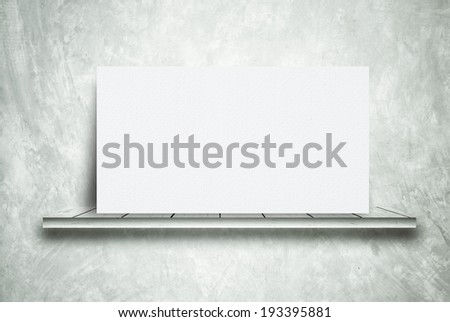 Shelf with white board on a cement wall. - stock photo