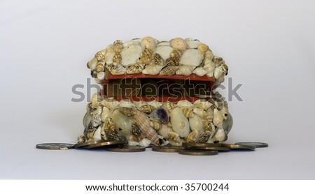 Shell covered chest with coins spilling out on white background - stock photo