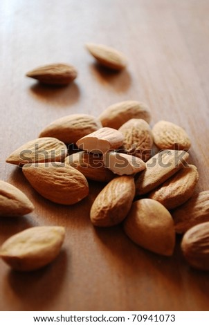 Shelled almonds on natural wooden table background - stock photo