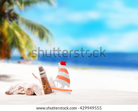 Shells on sandy beach with tropical beach background  - stock photo