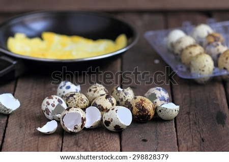 shells quail eggs and fried quail eggs on wooden background - stock photo