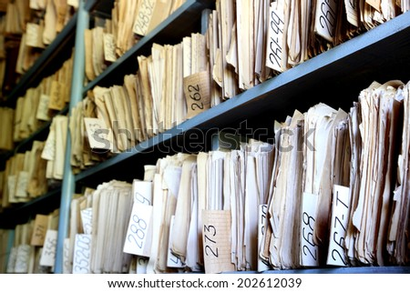 shelves full of files in an old archive - stock photo