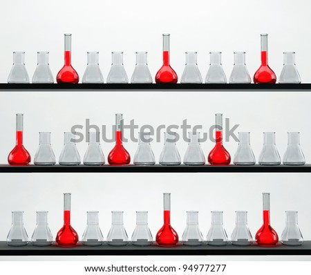 shelves in the chemistry laboratory with many flasks - stock photo