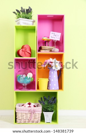 Shelves of different bright colors with decorative addition on wall background - stock photo
