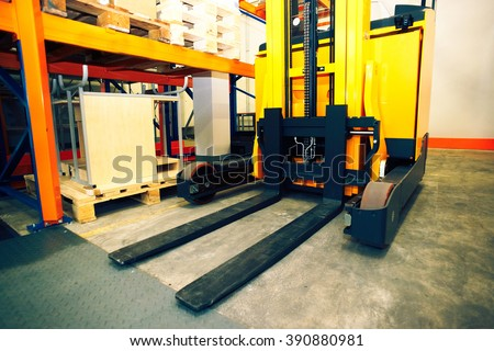 Shelves, racks and forklift  with pallets in distribution warehouse interior             - stock photo