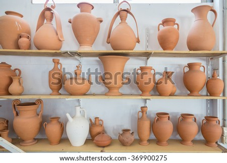 Shelves with different brown clay  jars and pots made by greek artists - stock photo
