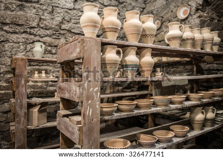 shelves with pottery in workshop - stock photo