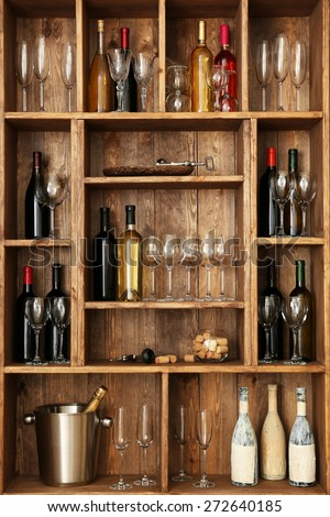 Shelving with wine bottles with glasses on wooden wall background - stock photo