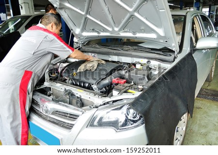 SHENGZHEN - OCT 17:Porfessional worker cleaning the car engine in toyota auto service garage,Shenzhen on Oct 17, 2013 in Shenzhen city,China.  - stock photo
